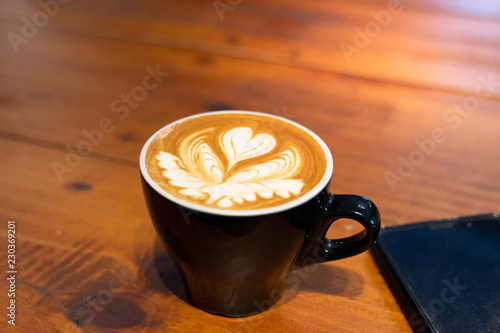 cup of coffee with latter art on wooden background Tableau sur Toile