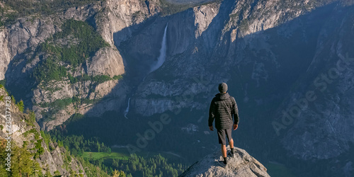 Photo  Man on cliff overlooking Yosemite Falls and valley