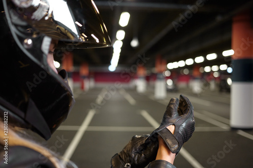 Unrecognizable woman getting prepared for motorcycle drive on parking lot, taking on black leather gloves. Night life, extreme sports, activity and people concept. Selective focus on woman's hands