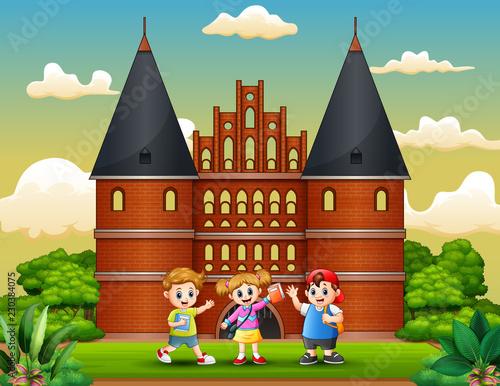 Poster Castle Cartoon of Happy school children standing in front of Holstentor building