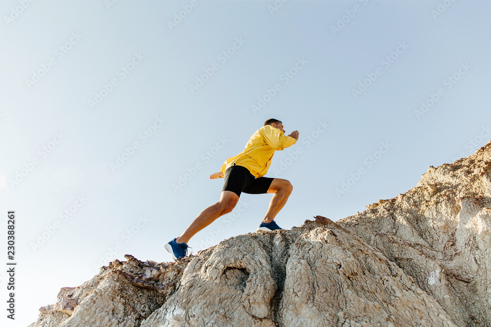 Fototapety, obrazy: concept to overcome difficulties. man in sports clothes climbing steep mountain