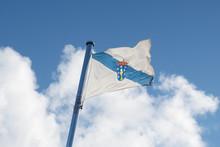 Flag Of Galicia Waving On The Sky On Cloudy Sky Spain