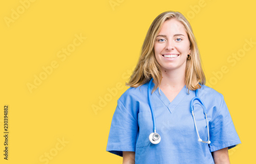 Fotografie, Obraz  Beautiful young doctor woman wearing medical uniform over isolated background with a happy and cool smile on face