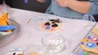 Time lapse. Step by step. Little girl decorating sugar skull cookies with royal icing for Dia de los Muertos holiday