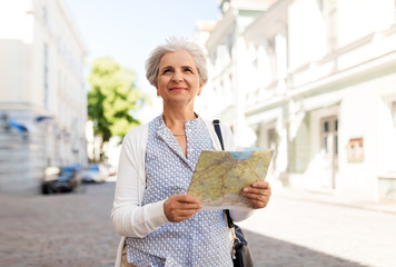 Fototapeta travel, tourism and retirement concept - senior woman or tourist with map on city street