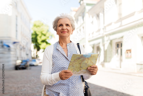 travel, tourism and retirement concept - senior woman or tourist with map on city street