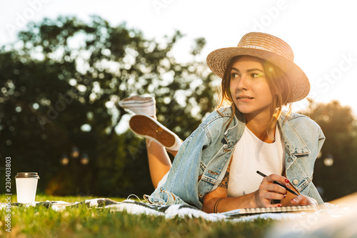 Lovely young girl laying on grass at the park