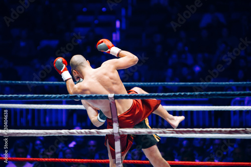 Photo  The boxer in the ring strikes the opponent in the arena of full light