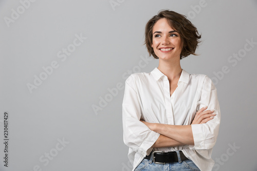 Obraz na plátně Happy young business woman posing isolated over grey wall background