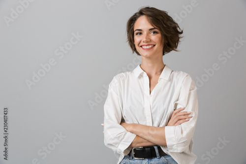 Obraz Happy young business woman posing isolated over grey wall background. - fototapety do salonu