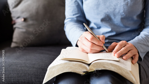 Photo Bible Study - Woman Taking Notes as She Reads from an Open Bible