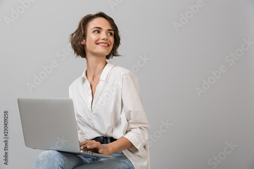 Obraz na plátně Young business woman posing isolated over grey wall background sitting on stool using laptop computer