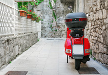Red Scooter Parked On The Empty Street.
