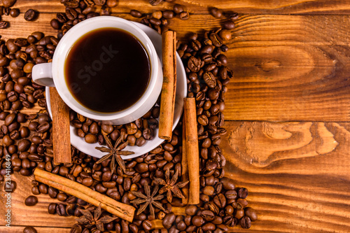 Cup of hot coffee, star anise, cinnamon sticks and scattered coffee beans on wooden table. Top view