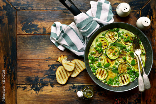 Omelette with grilled zucchini slices, sweet pea and mint.Top view with copy space.