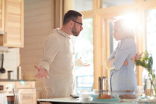 Young Married Caucasian Couple Arguing About Household Duties While Standing In Home Kitchen Illuminated With Bright Morning Sun