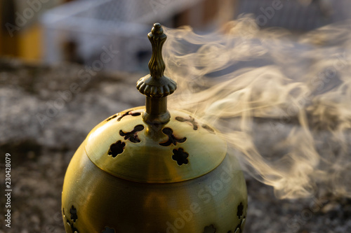 Slika na platnu incense burner censer with smoke and blurred background.