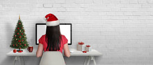 Christmas Greeting Card. The Girl Work On The Computer. Empty Space On A White Brick Wall For Text.