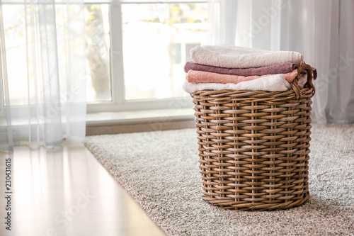 Fotografía  Wicker basket with folded clean towels on floor