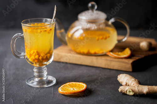 Foto op Aluminium Thee Sea buck thorn tea in glass teapot with glass cup and spoon, orange and ginger near on black background