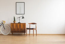 Stylish Chair Next To Retro Cabinet And Vintage Bike In Scandinavian Minimal Interior, Real Photo With Copy Space On The Wall