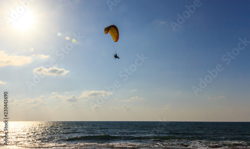 parachute jumper on motorized parachute flying over the sea at sunset