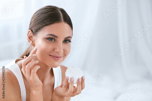 Fotografie, Obraz  Beauty. Beautiful Woman Applying Face Cream On Soft Facial Skin