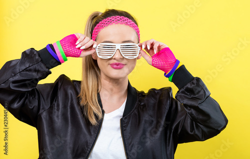 Tela  Woman in 1980's fashion with shatter shade glasses on a yellow background