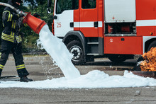 Partial View Of Firefighter Extinguishing Fire With Foam On Street