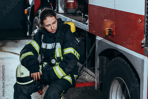 tired female firefighter in uniform with helmet sitting on truck at fire station Canvas Print