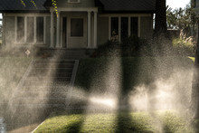 Sprinklers In Front Lawn Of California Home