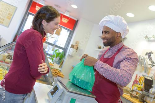 Zdjęcie XXL sprzedawca daje ciasto kobiecie