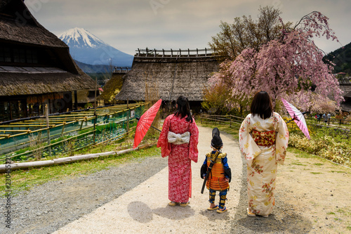 Poster Asia land Little samurai boy with sword and Two Kimono Japanese women at Saiko Iyashi no Sato Nenba, former farming, village near Mountain Fuji, Japan. Preserved wooden thatched roof houses near lake Saiko.