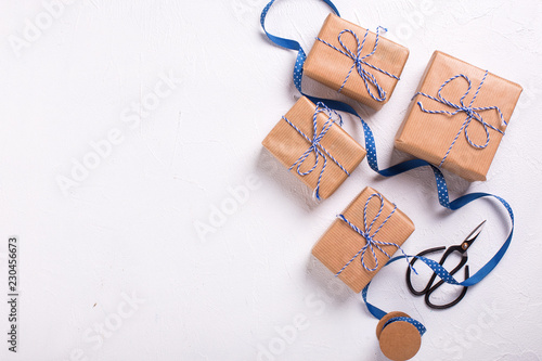 Wrapped gift boxes with presents, windmill, scissors and blue ribbon