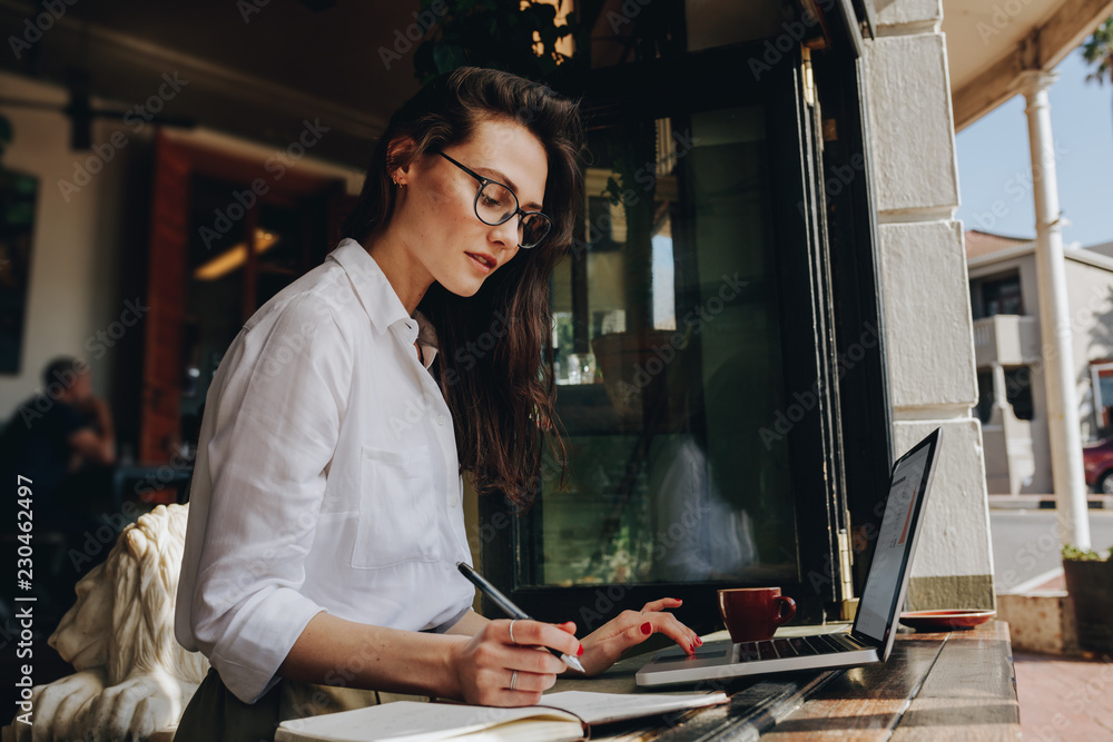 Fototapety, obrazy: Businesswoman working from a coffee shop
