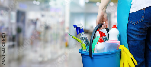 A cleaning woman is standing inside a building holding a bucket fulfilled with chemicals and facilities for tidying Canvas