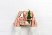 Woman Hands Give Wrapped Christmas Handmade Present In Paper With Christmas Decoration. Present Box On Holiday On Dark Wooden Table, Top View