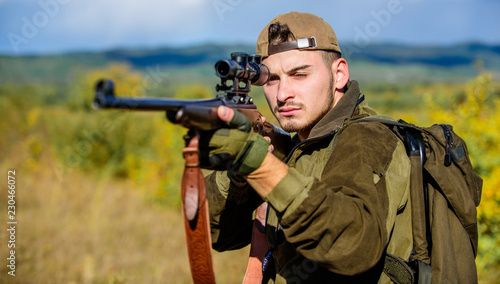 Man hunter aiming rifle nature background. Hunting skills and weapon equipment. Guy hunting nature environment. Hunting weapon gun or rifle. Hunting target. Looking at target through sniper scope