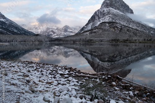 Fotografia, Obraz  Mt Grinnell reflected in Swiftcurrent Lake in the early dawn light after a snow storm