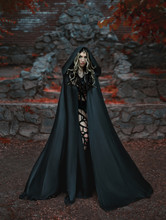 Medusa Gorgona Goddess Turning A Gaze Into A Stone. It Stands On The Background Of A Stone Throne With Red Bloodstains. The Dark Queen In A Black, Long Cloak With A Hood. Headed With Golden Snakes