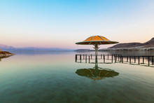 Sunset On The Dead Sea Shore, Bridge To An Umbrella Standing In The Sea Wate