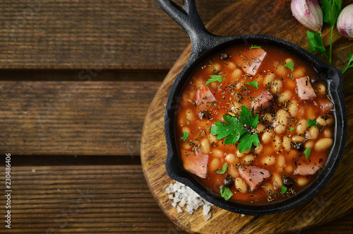 Baked beans on iron skillet on wooden table