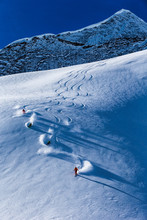 Four Skiers Skiing Down On Slope, British Colombia, Canada