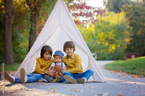 Foto  Children, sitting in a tent teepee, holding teddy bear toy with a nature autumn