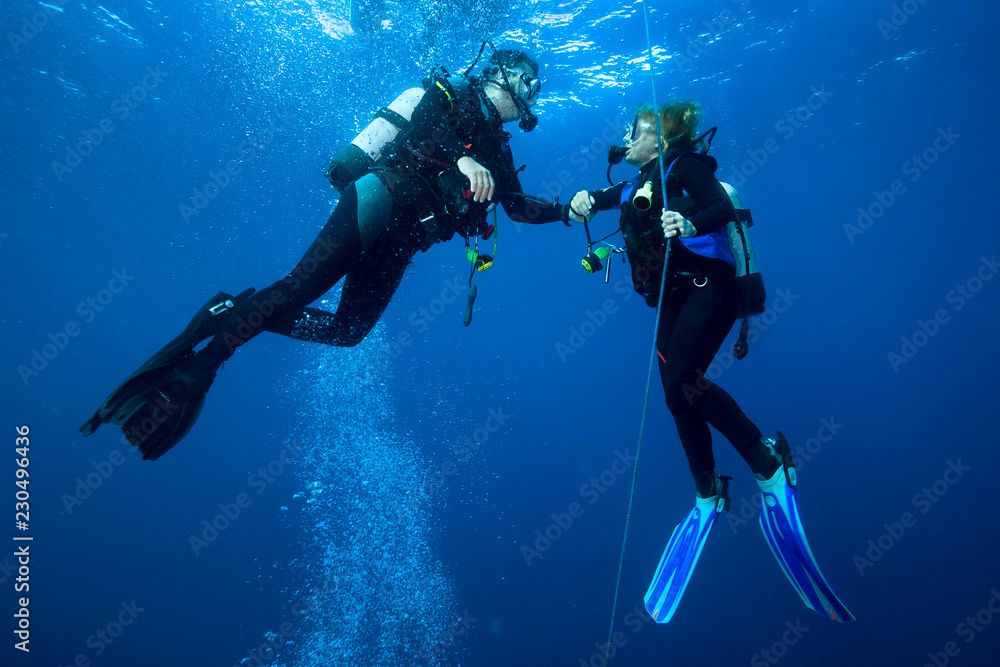Fototapeta Happy couple scuba divers  hovering together on a safety stop