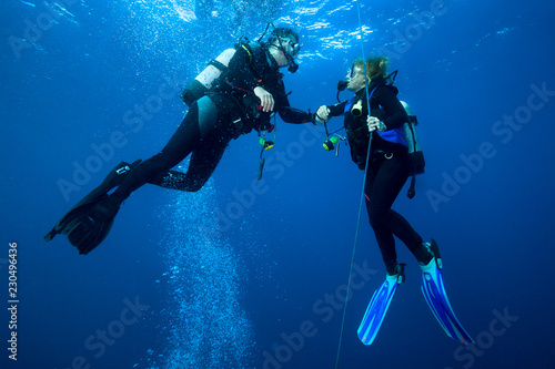 Poster Plongée Happy couple scuba divers hovering together on a safety stop