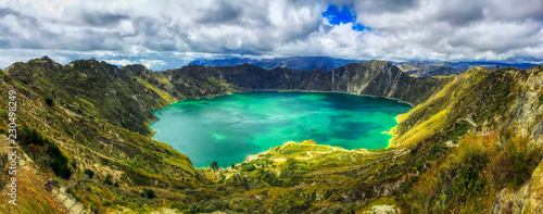 Poster Amérique du Sud A bird's eye panoramic view of the bright green volcanic Quilotoa Lake in Ecuador with lots of white and grey clouds in a blue sky and green brush on the side of the caldera
