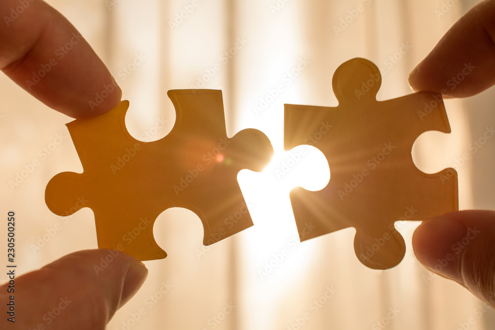 Fototapeta two hands trying to connect couple puzzle piece. with sunset background. symbol of association and connection, business strategy, completing, team support and help concept