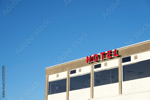 Fotografía  Hotel sign red letters and summer blue sky accommodation for tourists on holiday