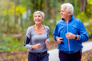Fototapeta Smiling senior active couple jogging together in the park